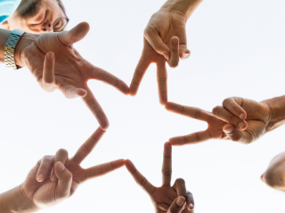 Image representing people joining hands evoking an example of non-commercial ad